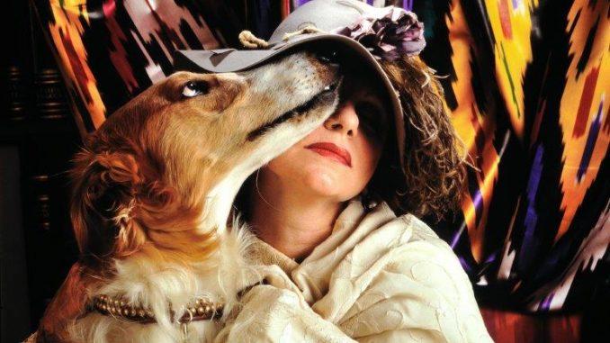 fotografia colori, la poetessa Evelina Schatz seduta con in braccio un cane marrone, vestita con scialle bianco e cappello con fiori e piume, sfondo tendaggio fantasia multicolore