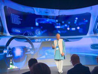 Fotografia dell'economista e professore bengalese Mohammad Yunus mentre parla all'uditorio di EY Digital Summit 2019. Yunus indossa abiti tradizionali del proprio paese, pantaloni lunghi chiari sotto una tunica celeste e un gilet chiaro.
