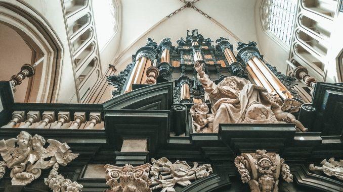 Abside di chiesa romana con organo e statue neoclassiche ripresa dal basso verso l'alto.