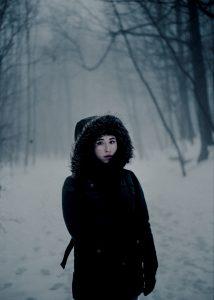 Ragazza con cappotto nero in paesaggio innevato