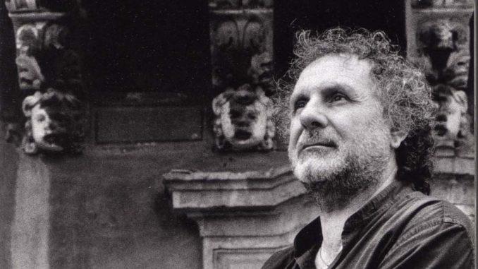 Angelo Scandurra ripreso di profilo, mezzo busto, capelli folti e ricci. Sullo sfondo i capitelli di un edificio barocco