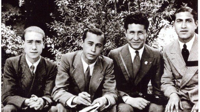 fotografia, bianco e nero, 4 giovani uomini in giacca e cravatta seduti su una panchina, sfondo cespugli di un giardino: Leonardo Sciascia con suoi compagni del Magistrale Superiore a Caltanissetta