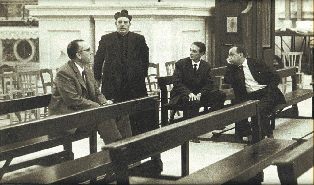 fotografia, bianco e nero, interno chiesa, 3 uomini in giacca e cravatta seduti sulle panche della chiesa, prete al centro in piedi