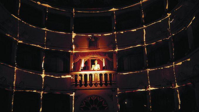 Scena al Teatro dei Coraggiosi, al centro l'attrice Giovanna Summo illuminata al centro su di una balconata