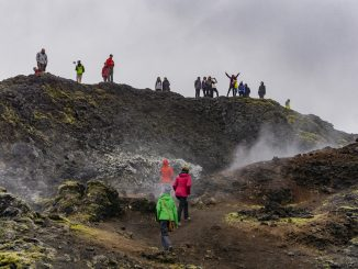 Tourists in a wild landscape shrouded in the fog. Some of them take pictures and selfies