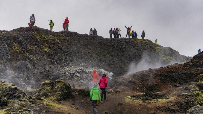 Turisti sparsi in uno scenario naturale selvaggio e avvolto dalla nebbia. Alcuni di loro fanno foto e scattano selfie.