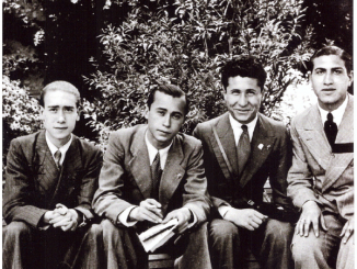 Black-and-white photography with 4 men in suits sitting on a bench, with shrubs on the background