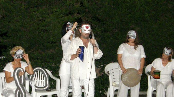 Fotografia della performance Ritual Rumore dell'artista Vitaldo Conte. Conte e il gruppo femminile T Rose, composto da quattro elementi, sono vestiti di bianco, sul volto indossano maschere durante la performance.