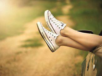 dal finestrino abbassato di un'automobile scura fuoriescono le gambe incrociate di un corpo femminile con scarpe sportive bianche.