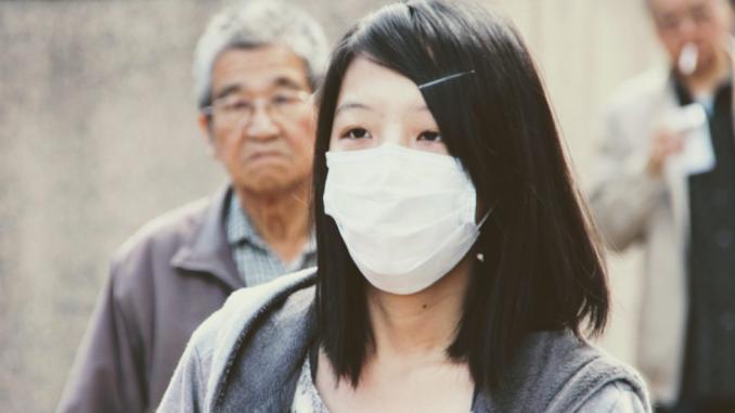 Una donna dai tratti asiatici indossa una mascherina bianca che copre il naso e la bocca. Dietro si intravedono due uomini