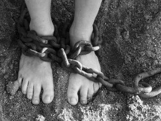 Una foto in bianco e nero mostra i piedi nudi di una persona poggiati sulla terra e immobilizzati da una catena