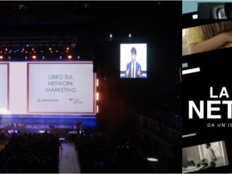"""Presentazione del libro """"La Via del Network"""" di Luigi Baccaro. Una foto mostra una sala piena di persone che assistono alla presentazione proiettata su un grande schermo centrale. Un primo piano dell'autore è mostrato su due schermi laterli più piccolo. A lato della foto, la copertina del libro"""