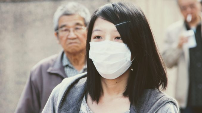 Image with an Asian girl wearing a white mask at to preserve herself from virus's attack.