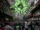 L'immagine mostra una affollata via cinese e sospesa sulle teste delle metaforicamente incombe una grande struttura verde che riproduce la struttura di un virus-