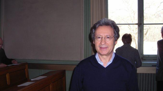 fotografia, colori, interno, ritratto di Angelo Gaccione scrittore italiano e poeta, in aula presso università di Ginevra, uomo brizzolato, occhiali, maglione blu e camicia azzurra