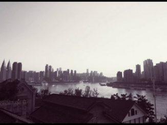 Fotografia in bianco e nero della città cinese Chongqing, in primo piano uno dei due fiumi che la attraversano,Yangtze e Jialing .
