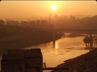 paesaggio urbano illuminato dalla luce rossastra del tramonto. Un corso d'acqua attraversa il paesaggio. Sullo sfondo sagome di grattacieli.