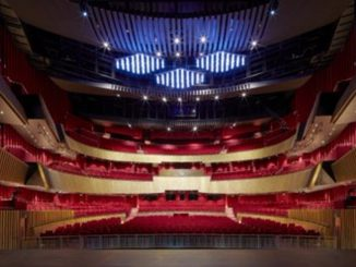 Interior of the Sheikh Jaber Al-Ahmed Cultural Center theater in Kuwait City, three-level hemicycle, with red armchairs and wooden structure.