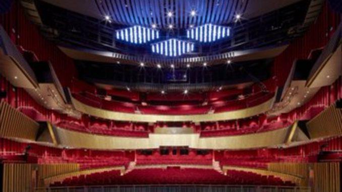 Interno del teatro Sheikh Jaber Al-Ahmed Cultural Centre di Kuwait City, emiciclo a tre livelli, con poltrone rosse e struttura in legno.