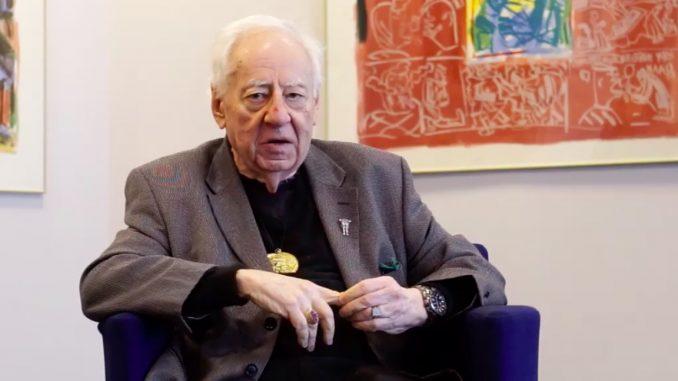 Il critico d'arte e poeta Edward Lucie-Smith seduto su una poltrona, sullo sfondo un'opera d'arte con colori accesi.