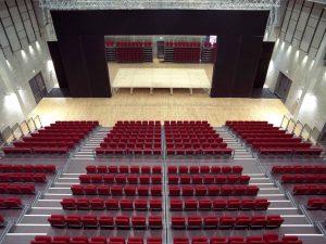 L'interno della ex Fonderia Limone riconvertito in spazio teatrale: uno spazioso palcoscenico e una platea degradante con molte file di poltrone rosse.