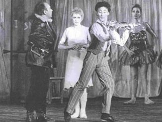 "The picture is a black and white photography that represent a scene from the ballet ""La Strada"" by and with Mario Pistoni. From Left to right Aldo Santambrogio (as Zampnò, dressed in black), Carla Fracci (as Gelsomina, dressed in white), Mario Pistoni (as the foul, dressed in strips and playing a violin). On the right, in front of a tarp that covers the backdrop, there are two ballet dancers dressed with sequin costumes"