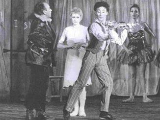 """L'immagine è una foto in bianco e nero che rappresenta un momento del balletto """"La Strada"""" di e con Mario Pistoni. Da destra a sinistra Aldo Santambrogio (Zampanò, vestito con giacca e pantaloni neri), Carla Fracci (Gelsomina, vestita interamente di bianco), Mario Pistoni (il Matto, vestito con abiti rigati e intento a suonare un violino). Sulla destra, davanti al telone che copre il fondale sono visibili due ballerine dai costumi coperti di lustrini"""