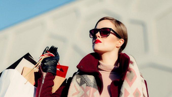 donna con capelli legati, occhiali da sole, rossetto sulle labbra e sguardo rivolto lateralmente regge nella mano destra una serie di buste di colori diversi. La donna indossa capi d'abbigliamento invernali: sciarpa, cappotto, guanti in pelle