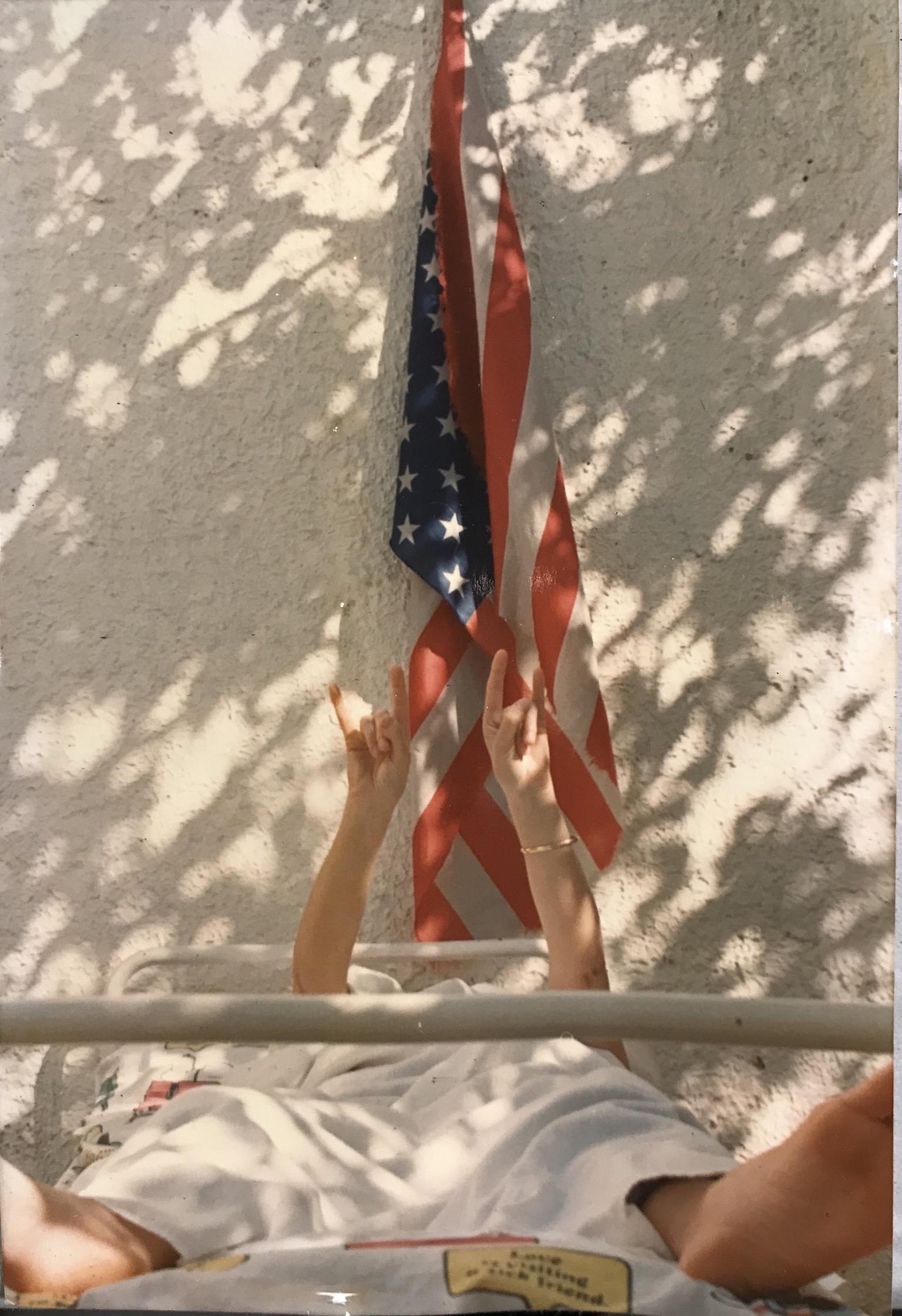 L'immagine mostra una donna vestita di bianco, sdraiata su un lettino, mentre con entrambe le mani fa il gesto delle corna. la scena si svolge all'aperto, davanti ad un muro bianco su cui è appesa una bandiera degli Stati Uniti d'America. Sul muro e sulla bandiera sono proiettate le ombre delle fronde di un albero