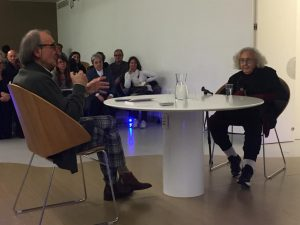 Photograph of the presentation of the autobiography of Nanda Vigo moderated by Carmelo Strano. The two are in a room, around a table, with an audience listening.