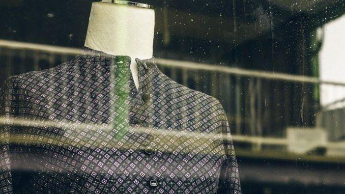 Attraverso una vetrina piuttosto sporca si intravede la parte superiore di un manichino senza testa. Il manichino indossa una camicia con i bottini neri e un pattern decorativo di piccoli rombi color viola e nero