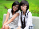 Due giovani ragazze dai tratti orientali, entrambe con occhiali da vista, posano sedute in un'area verde. Una di loro guarda verso l'osservatore, l'altra rivolge lo sguardo lateralmente