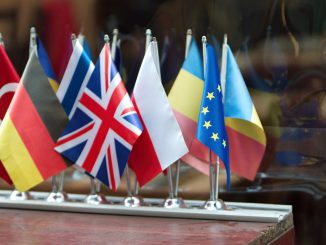 Su un tavolo di legno, di fronte ad una superficie riflettente sono disposte dodici bandierine. quelle riconoscibili sono -da sinsitra verso destra- Turchia, Germania, Grecia, Regno Unito, Polonia, Moldavia, Unione Europea e Romania