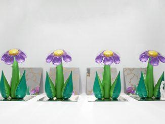 Quattro oggetti in plastica gonfiabile dalla forma di fiori con i petali viola sono disposti sopra quattro specchi