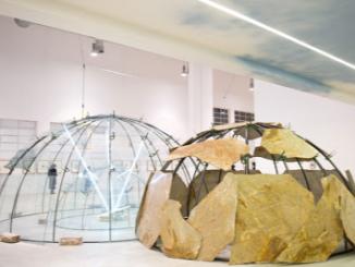 due strutture a forma di igloo. Una è esternamente trasparente e contiene all'interno delle lastre luminose, un'altra è parzialmente ricoperta da pezzi di materiale simile a cartone