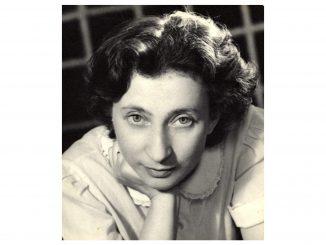 foto in bianco e nero e in primo piano di una donna con lo sguardo rivolto verso l'osservatore e il mento appoggiato sulla mano
