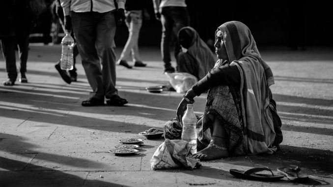 The picture is a black and white photography. The image shows an indian road with several people walking around. In the foreground, a barefoot woman, dressed in poor clothes is sitting on the ground, with a pair of sandal, a bottle of water and some little bowl with seeds inside. Another sitting woman can be seen in the background. Both the women are overlooked by the passers-by