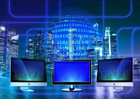 Tre monitor accesi da cui fuoriescono dei sottili fasci di luce blu. Al centro un gruppo di cifre luminose con alternanza di 0 e 1. Sullo sfondo grattacieli illuminati