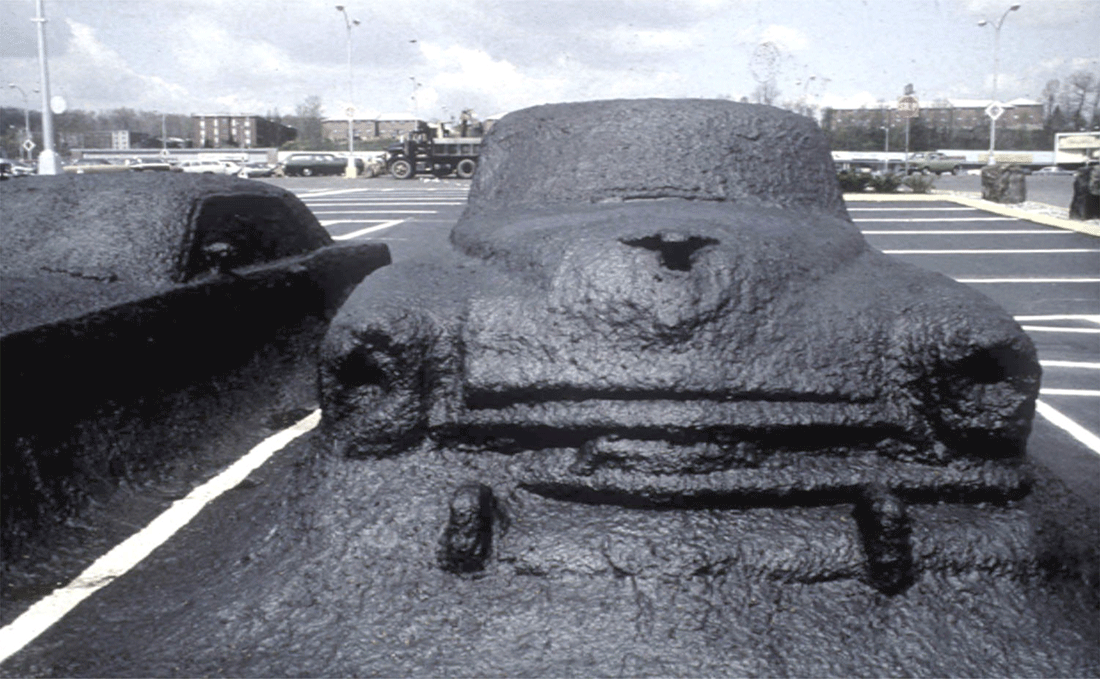 A James Wines's photo: in a large parking lot a car is completely covered with asphalt, merged with the pavement and immobilized.