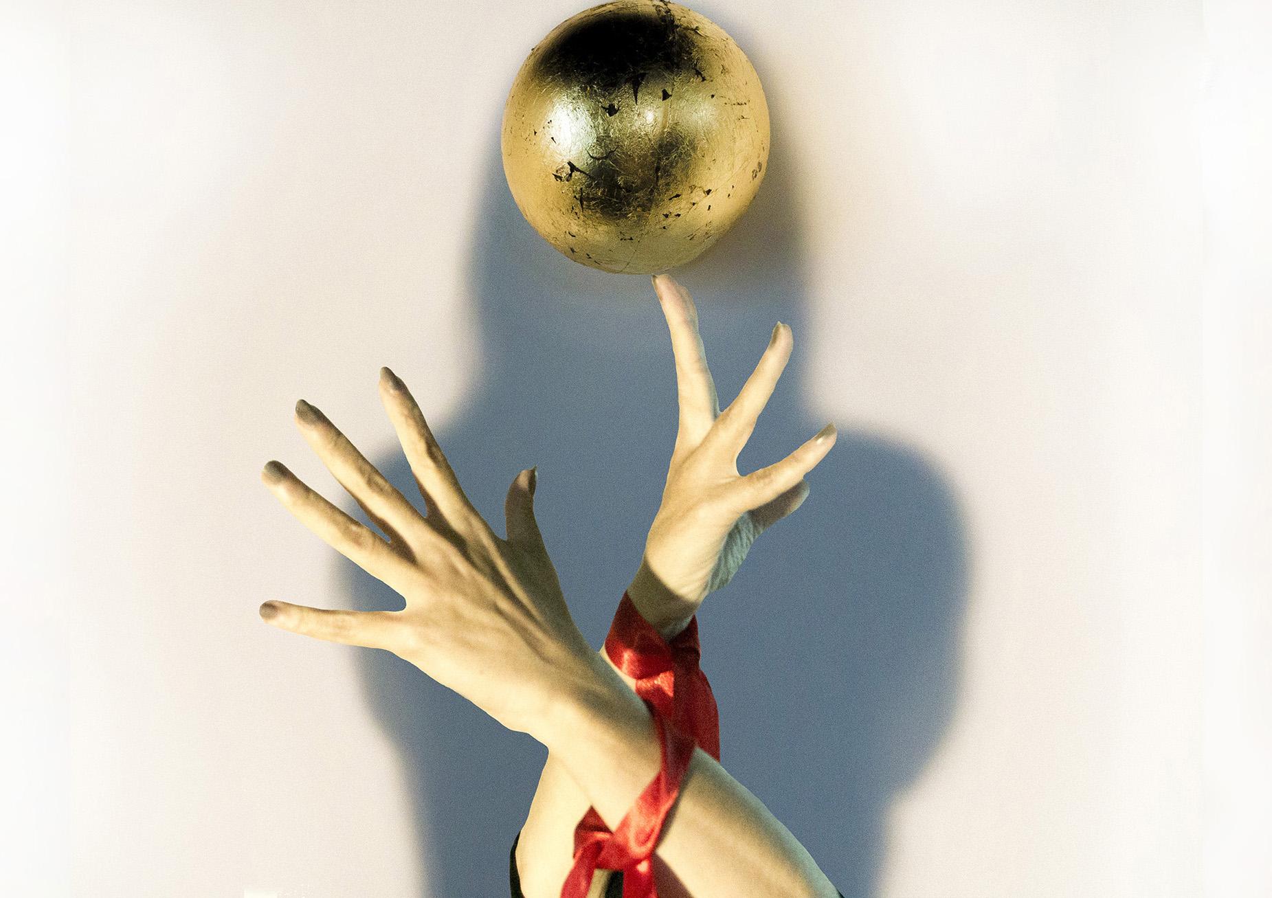 fotografia a colori, opera di artista Marilena Vita, mani con polsi legati da nastro rosso, sfera dorata che fluttua