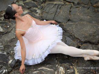 fotografia, esterno, colori, ballerina in tutù bianco seduta su rocce nere, filosofia della danza