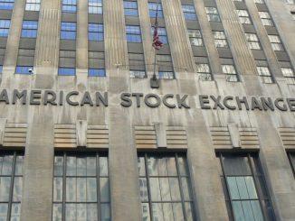 La foto mostra la sede dell'American Stock Exchangge building, un edificio grigio in stile Art decò, pieno di finestree con una bandiera statunitense appessa ad un pinnacolo al centro
