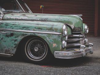 La foto mostra la parte anteriore di un'auto verde anni '50. la vernice è in gran parte sbiadita e la vettura si presenta in generale in condizioni pessime. Sullo sfondo è visibile un garage dal portone arruginito