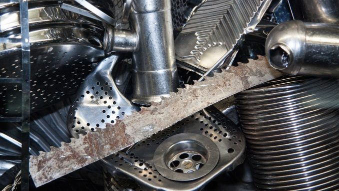 The photo shows several metal scraps, including a sawtoothed blade, a pipe, a pedal and a sink pipe union