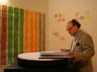 Man with glasses browsing a book. In front of him a drawing hangs on the wall with red, green, orange and brown strips