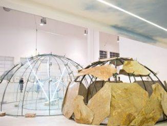 due strutture a forma di igloo, una trasparente con delle lastre luminose visibili all'interno, l'altra circondata da pezzi irregolari di un materiale marrone