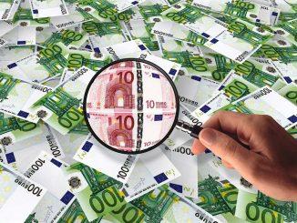l'immagine mostra un tappeto di banconote da cento euro bianche e verdi. Una mano che spunta dal basso a destra, tiene in mano una lente d'ingrandimento nera che, puntata al centro, rivela delle banconote da dieci euro