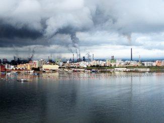scenario urbano con palazzi e ciminiere di fabbriche affacciato sul mare. Dalle ciminiere fuoriescono fumi che rendono grigio il cielo