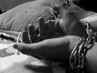 l'immagine è una foto in bianco e nero che mostra un paio di mani incatenate vicino ad un cuscino sopra un materasso con decorazioni infantili
