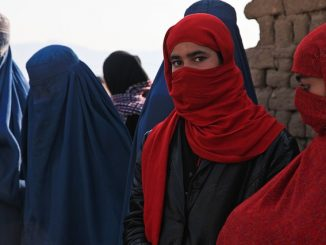 The photo shows several afghan women whose face is covered with a veil as in many muslim countries. The figures in the background wear traditional black and blue burqa. the two girl in the foreground, instead, wear a simpler red scarf that allows to see the eyes